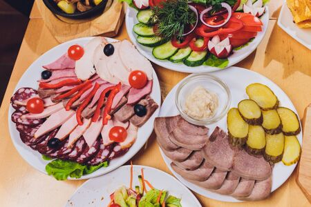 Food tray with delicious salami, pieces of sliced ham, sausage and salad. Meat platter with selection on table.