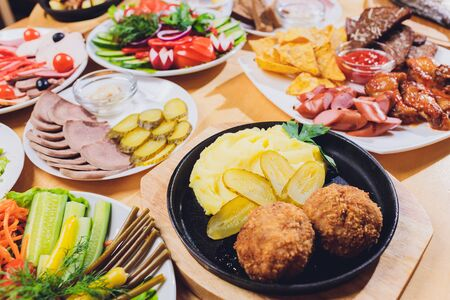 Dining table with a variety of snacks and salads. Salmon, olives, wine, vegetables, grilled fish toast. The concept of a family celebratory dinner. Thanksgiving, Christmas. top veiw