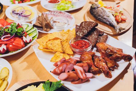 Dining table with a variety of snacks and salads. Salmon, olives, wine, vegetables, grilled fish toast. The concept of a family celebratory dinner. Thanksgiving, Christmas. top veiw. Stock fotó