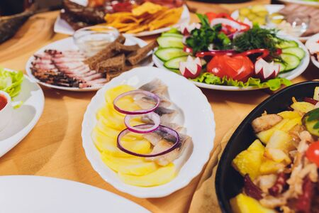 Food tray with delicious salami, pieces of sliced ham, sausage and salad. Meat platter with selection on table Stock Photo - 131358112