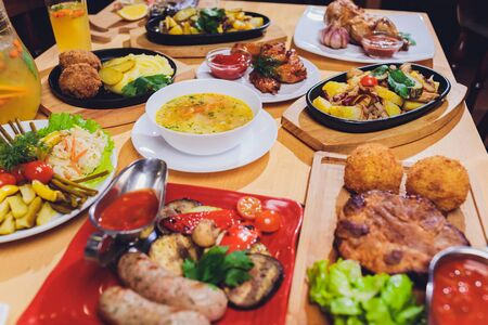 Dinner table with meat grill, roast new potatoes, vegetables, salads, sauces, snacks and lemonade, top view. Stock Photo - 131362929