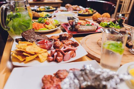 Dinner table with meat grill, roast new potatoes, vegetables, salads, sauces, snacks and lemonade, top view.