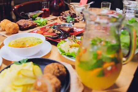 Esstisch mit Fleischgrill, Bratkartoffeln, Gemüse, Salaten, Saucen, Snacks und Limonade, Draufsicht.
