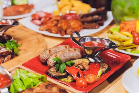Dinner party food concept. Dinner table with grilled sausage, tortilla wraps, beer drink and different dishes on wooden table, rustic style.