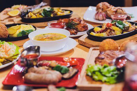 Concepto de comida de fiesta de cena. Mesa con salchicha a la parrilla, envolturas de tortilla, bebida de cerveza y diferentes platos en la mesa de madera, estilo rústico Foto de archivo