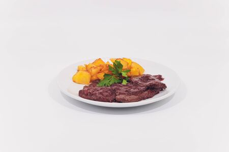 Grilled steaks, boiled potatoes and vegetable salad on white background.