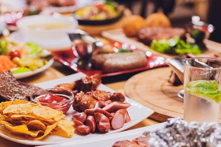 Dinner party food concept. Dinner table with grilled sausage, tortilla wraps, beer drink and different dishes on wooden table, rustic style
