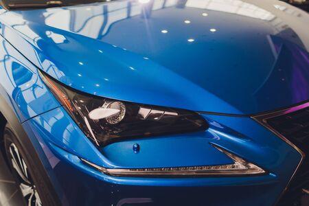 Closeup headlights of car blue body close-up. gray body