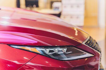Closeup headlights of car red body close-up.