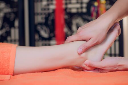 reflexology foot massage, spa foot treatment close-up