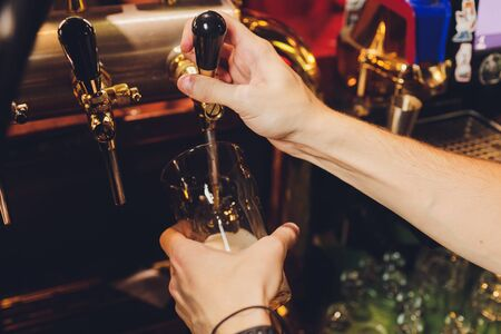 close-up of barman hand at beer tap pouring a draught lager beer Stock Photo