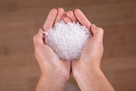 Piccole palline di plastica sul dito.Micro plastica. inquinamento dell'aria