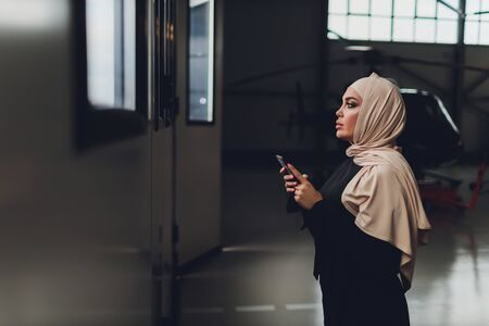 Elegant business muslim arab woman near the helicopter. Business, success and luxury concept. helicopter hangar
