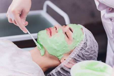 Upper view of a womansUpper view of a woman's face covered by alginate mask while leaning on a spa bed