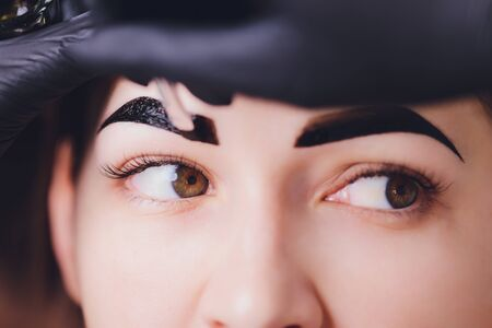 schoonheidsspecialiste-make-up artiest past verfhenna toe op eerder geplukte, ontwerp, getrimde wenkbrauwen in een schoonheidssalon in de sessiecorrectie. Professionele verzorging voor het gezicht.