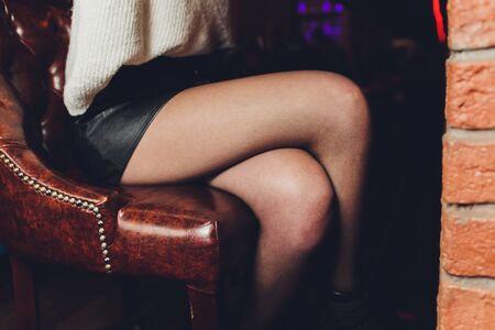 Beautiful female legs in black pantyhose in a restaurant