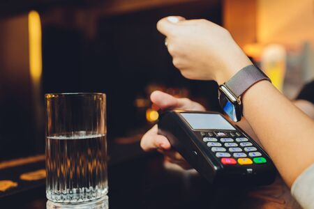 Woman pay by smart watch with NFC technology