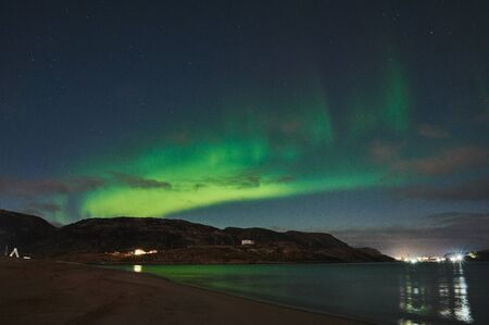 Zorza polarna nad oceanem. Zorza polarna w Teriberce w Rosji. Gwiaździste niebo z polarnymi światłami i chmurami. Nocny zimowy krajobraz z zorzą polarną, morze z kamieniami w niewyraźnej wodzie, ośnieżone góry. Podróż