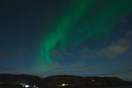 바다 위의 오로라. 러시아 테리베르카의 북극광. 극광과 구름이 있는 별이 빛나는 하늘. 오로라가 있는 밤 겨울 풍경, 흐릿한 물에 돌이 있는 바다, 눈 덮인 산. 여행 스톡 콘텐츠