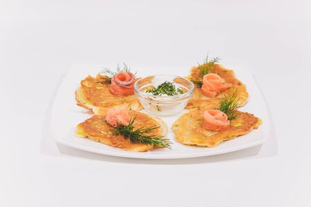 A plate of potato pancakes decorated with basil leaves on the table Stock Photo