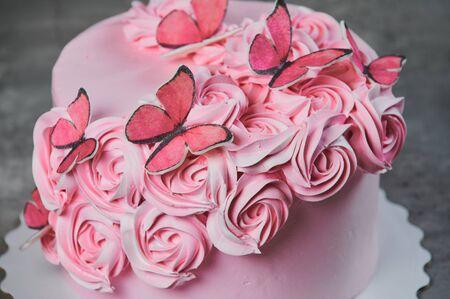 Widok z góry świeżo upieczonego ciasta ozdobionego różowymi różami cukru pudru wyświetlanego na stojaku na ciasto na czarnym tle z copyspace.