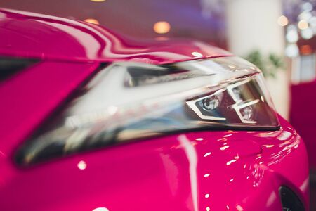 Close up shot headlight in luxury pink car background. Modern and expensive sport car concept