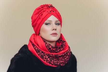Photo of self assured Arabian lady in hijab, shows you right way, points at blank space with both fore fingers, invites going there, promots copy space. Check it out with me.
