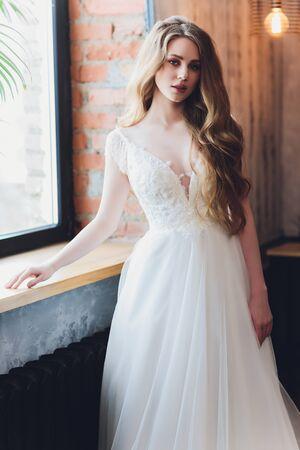 Die schöne Frau, die in einem Hochzeitskleid aufwirft.