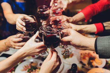 Immagine ravvicinata di un gruppo di persone che tintinnano bicchieri con vino o champagne davanti a sfondo bokeh. le mani delle persone anziane.