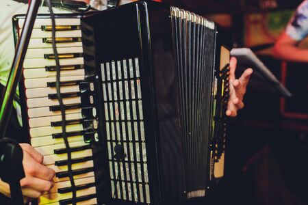 Image of musician playing on accordion closeup.