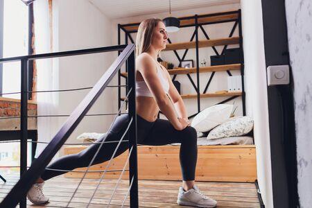 Aantrekkelijke fitnessvrouw die thuis rekoefeningen doet, als onderdeel van een gezonde levensstijl zonder naar de sportschool te gaan