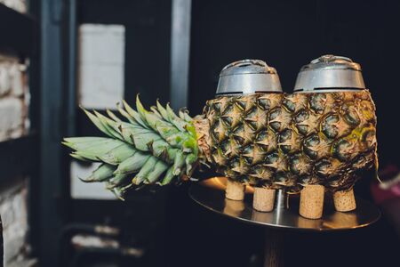 Luxury hookah with pineapple. Exotic bowl with fruit. Hookah lounge. Fruits and coals. Glamours relax. Narghile and water pipe