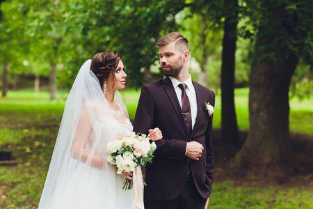 feliz novia y el novio en un parque el día de su boda. Foto de archivo