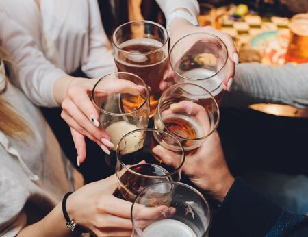 Close up shot of group of people clinking glasses with wine or champagne in front of bokeh background. older people hands