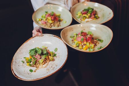 Waiter carrying a plate with fish and salad on a wedding.
