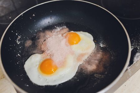 Appetizing photograph of scrambled eggs from one chicken egg in a pan with boiling sunflower oil.