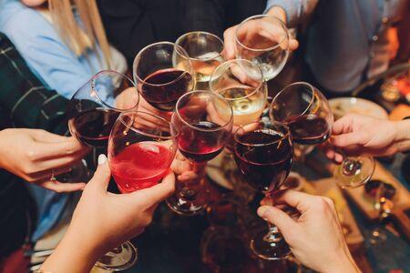 Bliska strzał grupy ludzi brzęk kieliszków z winem lub szampanem przed bokeh tle. ręce osób starszych.