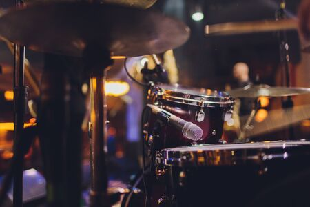 The man is playing drum set in low light background Stock Photo