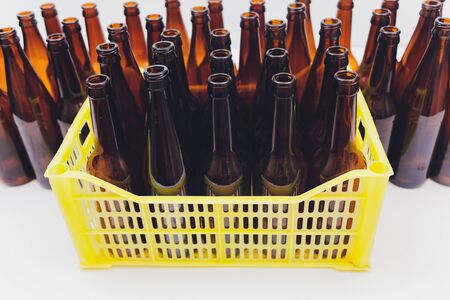 Dusty vintage yellow beer crate with empty brown beer bottles on white background Stock Photo