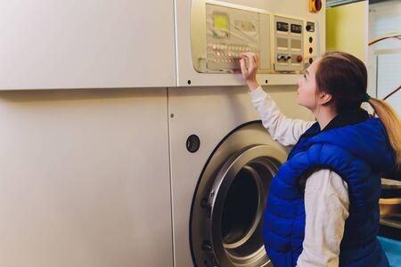 Young woman pressing buttons on washing machine in dry-cleaning.