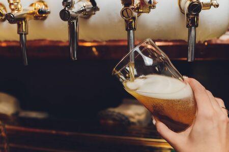 Barista che tira una pinta di birra dietro il bancone.