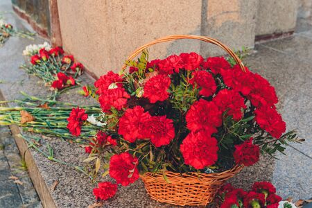 Red carnations near the monument as a symbol of memory.