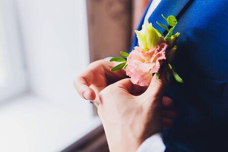 Boutonniere on groom's wedding jacket. White and pink rose wedding boutonniere on suit of groom