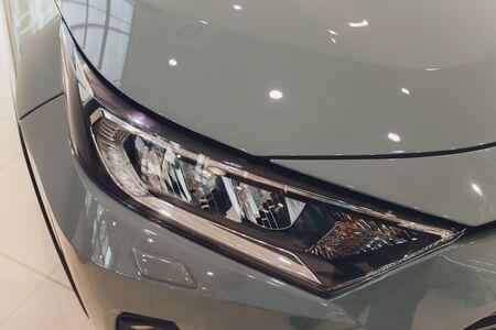 Closeup headlights of car white body close-up gray body Standard-Bild