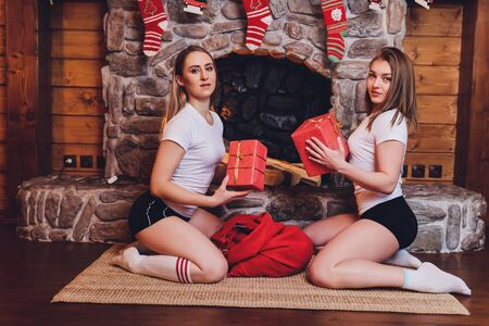 Two girls girlfriends in pajamas unpack gifts under the Christmas tree.