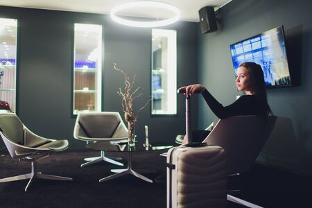 Businesswoman sitting at the airport lounge, waiting for the flight. Thoughtful woman sitting on sofa at airport waiting area.