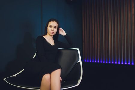 Elegant beautiful woman in a black cocktail dress and high heels sitting in a contemporary armchair.