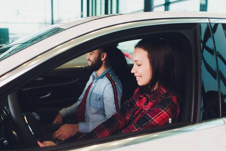 Visiting car dealership. Beautiful couple is talking and smiling while sitting in their new car. Woman driving her new car at the dealer