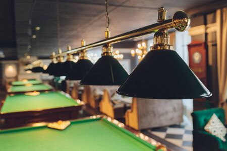 lamp over billiards green table balls and cues