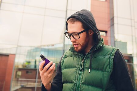 Portrait of young guy with large beard in glasses vaping an electronic cigarette opposite urban background.